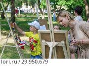 Купить «The girl artist teaches children to draw in a public park. 06/29/2018: Photo taken in Russia, Orenburg city, Perovsky Park», фото № 29950679, снято 29 июня 2018 г. (c) Вадим Орлов / Фотобанк Лори