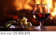 Купить «A glass of brandy and plate with cheese and lemon are on the table on the background of a burning fireplace», видеоролик № 29950875, снято 12 февраля 2019 г. (c) Алексей Кузнецов / Фотобанк Лори