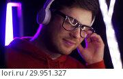 Купить «man in headphones over neon lights of night club», видеоролик № 29951327, снято 11 февраля 2019 г. (c) Syda Productions / Фотобанк Лори