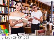 Купить «girl browsing textbooks in bookstore», фото № 29951555, снято 18 января 2018 г. (c) Яков Филимонов / Фотобанк Лори