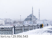 TURKEY, ISTANBUL, JANUARY 07, 2017: Unidentified men fishing at the galata bridge on the heaviest snowfall in Istanbul,Turkey. Стоковое фото, фотограф Isa Özdere / easy Fotostock / Фотобанк Лори