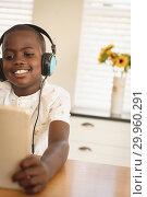 Купить «African American boy playing game on digital tablet at dining table in kitchen», фото № 29960291, снято 7 ноября 2018 г. (c) Wavebreak Media / Фотобанк Лори