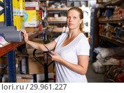 Young woman standing near racks in build store bebore buying tools. Стоковое фото, фотограф Яков Филимонов / Фотобанк Лори