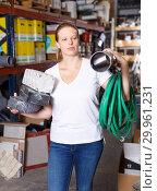 Купить «Woman customer holding purchases and walking in modern build store», фото № 29961231, снято 20 сентября 2018 г. (c) Яков Филимонов / Фотобанк Лори