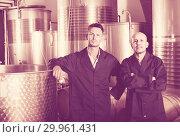 Купить «Two friendly men in uniforms standing in winery fermentation compartment», фото № 29961431, снято 15 сентября 2019 г. (c) Яков Филимонов / Фотобанк Лори