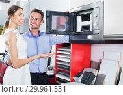 Купить «Adult man and woman are choosing new microwave», фото № 29961531, снято 15 июня 2017 г. (c) Яков Филимонов / Фотобанк Лори