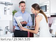 Купить «Glad assistant working with customer in store», фото № 29961535, снято 15 июня 2017 г. (c) Яков Филимонов / Фотобанк Лори