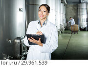 Купить «Female winery employee in uniform taking off data», фото № 29961539, снято 19 марта 2019 г. (c) Яков Филимонов / Фотобанк Лори