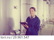 Купить «Female winery employee in uniform taking off data», фото № 29961547, снято 20 марта 2019 г. (c) Яков Филимонов / Фотобанк Лори