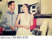 Купить «Couple choosing microwave in household appliance section», фото № 29961619, снято 15 июня 2017 г. (c) Яков Филимонов / Фотобанк Лори