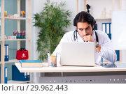 Купить «Young handsome doctor in telemedicine concept», фото № 29962443, снято 12 ноября 2018 г. (c) Elnur / Фотобанк Лори