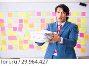 Купить «Young handsome employee with many conflicting priorities», фото № 29964427, снято 16 октября 2018 г. (c) Elnur / Фотобанк Лори