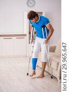Купить «Leg injured young man with crutches at home», фото № 29965647, снято 19 сентября 2018 г. (c) Elnur / Фотобанк Лори