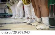 Sport competition. Cheerleading women standing indoors and waving with a pom poms. White socks and sneakers. Стоковое видео, видеограф Константин Шишкин / Фотобанк Лори