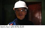 Купить «A young man engineer walking in manufacturing plant and looking around», видеоролик № 29970531, снято 16 февраля 2019 г. (c) Константин Шишкин / Фотобанк Лори