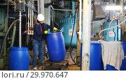 Купить «A man engineer in manufacturing plant rolls a cart with a barrel and removes it on the floor», видеоролик № 29970647, снято 16 февраля 2019 г. (c) Константин Шишкин / Фотобанк Лори