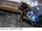 Мужчина сидит на лавке в парке рядом с детской коляской в городе Москве, Россия (2019 год). Редакционное фото, фотограф Николай Винокуров / Фотобанк Лори