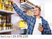 Купить «Man purchasing peanut butter in grocery», фото № 29978235, снято 15 октября 2016 г. (c) Яков Филимонов / Фотобанк Лори