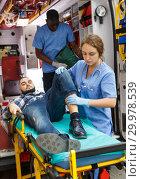Купить «Paramedic team providing first aid to man», фото № 29978539, снято 30 ноября 2018 г. (c) Яков Филимонов / Фотобанк Лори