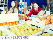 Купить «Portrait of young customer selecting apple in grocery», фото № 29978683, снято 1 марта 2017 г. (c) Яков Филимонов / Фотобанк Лори