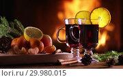 Купить «Two glasses of mulled wine (gluhwein) and a plate of fruit on the background of a burning fireplace», видеоролик № 29980015, снято 17 февраля 2019 г. (c) Алексей Кузнецов / Фотобанк Лори