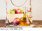 Купить «Processing of an agricultural crop of red and green apples. Homemade preparations, healthy diet vegetarian food. Spiced apple cider vinegar, juice, cider in a glass jug next to a box of ripe fruit», фото № 29980375, снято 16 февраля 2019 г. (c) Светлана Евграфова / Фотобанк Лори