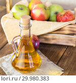 Купить «Processing of an agricultural crop of red and green apples. Homemade preparations, healthy diet vegetarian food. Spiced apple cider vinegar, juice, cider in a glass jug next to a box of ripe fruit», фото № 29980383, снято 16 февраля 2019 г. (c) Светлана Евграфова / Фотобанк Лори