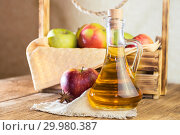Processing of an agricultural crop of red and green apples. Homemade preparations, healthy diet vegetarian food. Spiced apple cider vinegar, juice, cider in a glass jug next to a box of ripe fruit. Стоковое фото, фотограф Светлана Евграфова / Фотобанк Лори
