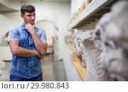 Купить «Man looking at stone architectural elements», фото № 29980843, снято 19 августа 2018 г. (c) Яков Филимонов / Фотобанк Лори