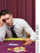 Купить «Man drinking whiskey at poker table», фото № 29996951, снято 20 июля 2012 г. (c) Wavebreak Media / Фотобанк Лори