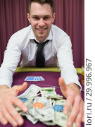 Купить «Happy man at poker table taking his winnings», фото № 29996967, снято 20 июля 2012 г. (c) Wavebreak Media / Фотобанк Лори