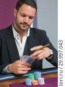 Купить «Man holding a cigar looking at his cards», фото № 29997043, снято 20 июля 2012 г. (c) Wavebreak Media / Фотобанк Лори