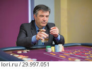 Купить «Man looking at the roulette table looking angry», фото № 29997051, снято 20 июля 2012 г. (c) Wavebreak Media / Фотобанк Лори