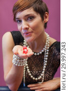 Купить «Woman holding and blowing on dice for luck», фото № 29997243, снято 20 июля 2012 г. (c) Wavebreak Media / Фотобанк Лори
