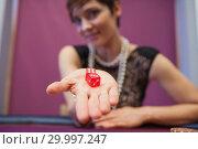 Купить «Woman holding dices at table», фото № 29997247, снято 20 июля 2012 г. (c) Wavebreak Media / Фотобанк Лори