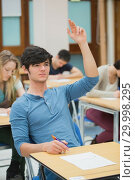 Купить «Student raising hand during exam», фото № 29998295, снято 25 июля 2012 г. (c) Wavebreak Media / Фотобанк Лори