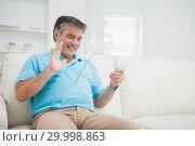 Купить «Smiling man waving at clear pane acting as digital tablet pc», фото № 29998863, снято 31 июля 2012 г. (c) Wavebreak Media / Фотобанк Лори
