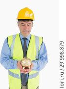 Купить «Architect holding a piggy bank», фото № 29998879, снято 31 июля 2012 г. (c) Wavebreak Media / Фотобанк Лори