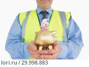 Купить «Man in vest holding a piggybank», фото № 29998883, снято 31 июля 2012 г. (c) Wavebreak Media / Фотобанк Лори