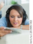 Купить «Woman listening music and looking at cd on sofa», фото № 29999143, снято 16 августа 2012 г. (c) Wavebreak Media / Фотобанк Лори