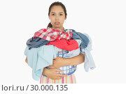 Купить «Frowning woman holding basket which is full of dirty laundry», фото № 30000135, снято 8 августа 2012 г. (c) Wavebreak Media / Фотобанк Лори