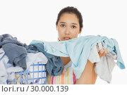 Купить «Frowning woman taking out dirty laundry », фото № 30000139, снято 8 августа 2012 г. (c) Wavebreak Media / Фотобанк Лори