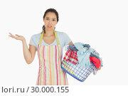 Купить «Puzzled young woman holding laundry basket full of dirty laundry», фото № 30000155, снято 8 августа 2012 г. (c) Wavebreak Media / Фотобанк Лори