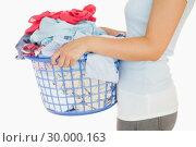 Купить «Woman holding a basket overflowing of laundry», фото № 30000163, снято 8 августа 2012 г. (c) Wavebreak Media / Фотобанк Лори