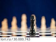 Купить «Black chess piece standing at the chessboard white ones behind», фото № 30000743, снято 28 февраля 2012 г. (c) Wavebreak Media / Фотобанк Лори