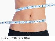 Купить «Fit belly surrounded by measuring tape», фото № 30002899, снято 19 апреля 2013 г. (c) Wavebreak Media / Фотобанк Лори