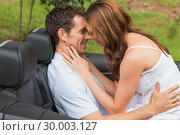 Купить «Young couple feeling romantic in back seat», фото № 30003127, снято 6 апреля 2013 г. (c) Wavebreak Media / Фотобанк Лори