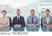 Купить «Stern business people sitting straight looking at camera», фото № 30003507, снято 7 апреля 2013 г. (c) Wavebreak Media / Фотобанк Лори