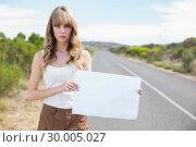 Купить «Serious pretty woman holding sign while hitchhiking », фото № 30005027, снято 26 апреля 2013 г. (c) Wavebreak Media / Фотобанк Лори