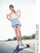 Купить «Young woman making rock and roll gesture while balancing on her skateboard», фото № 30005127, снято 26 апреля 2013 г. (c) Wavebreak Media / Фотобанк Лори